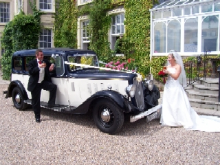 Bride and groom face each other across the bonnet of the car